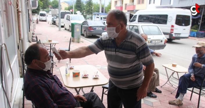 Çay ocağı işletmecisi, müşterilerine ateşlerini ölçtükten sonra servis yapıyor