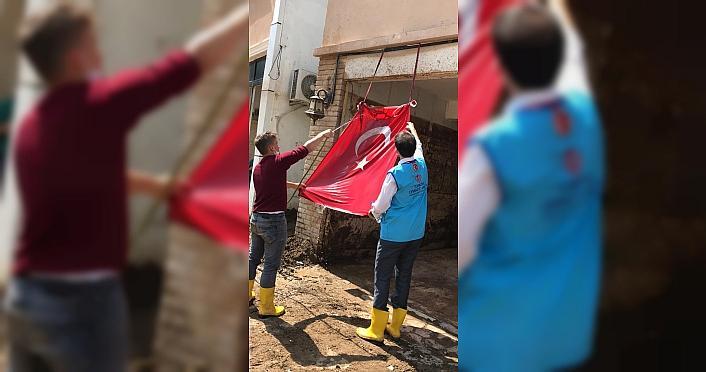 Diyanet görevlilerinin, çamur olan Türk bayrağını temizleme anları kameraya yansıdı