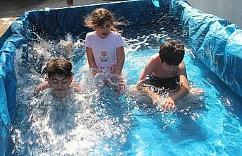 Amasya'da köy çocukları traktör römorkunu havuza çevirdi